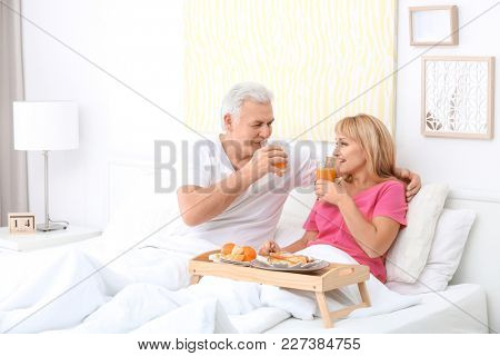 Mature couple having breakfast in bed. Romantic morning
