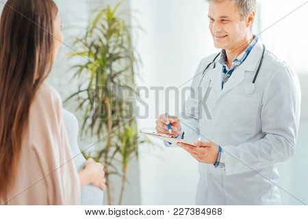 Monthly Checkup. Selective Focus On A Medical Worker Smiling While Looking At An Expectant Mother An