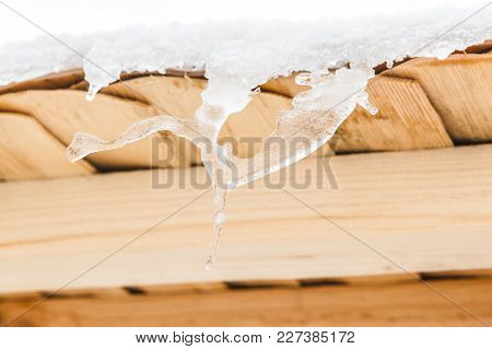 Wonderful Icicles Melt On The Wooden Roof At The End Of Winter And Water Drops Are Fall Down. Spring