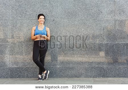 Woman Choose Music To Listen In Her Mobile Phone During Workout In City, Having Rest And Leaning At