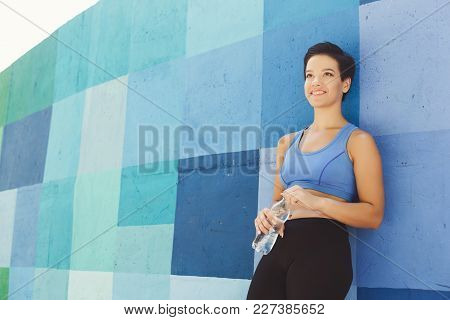Young Woman Runner Is Having Break, Drinking Water While Jogging In City, Leaning At Blue Painted Wa