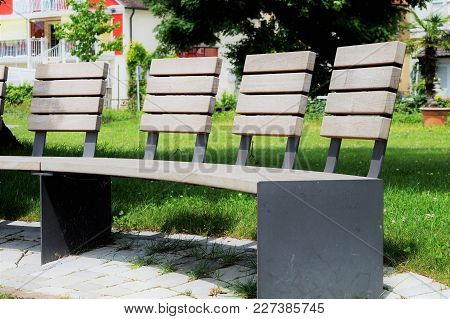 Save Download Preview Lonely Bench In A Park. Park Bench, Concept Of A Weekend And Relaxation. A Par