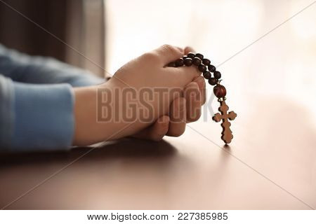 Little boy holding wooden cross at table