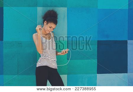Happy Smiling African-american Woman Leaning On Bright Blue Graffiti Wall, While Listening Music, Re