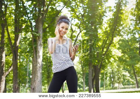 Happy Smiling African-american Woman Posing In Sunny Summer Park, While Listening Music, Relaxing Fr