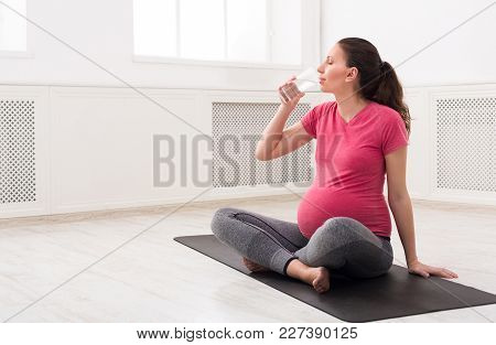 Young Pregnant Woman Drinking Water, Practicing Yoga. Expectant Female Holding Glass, Rest After Tra
