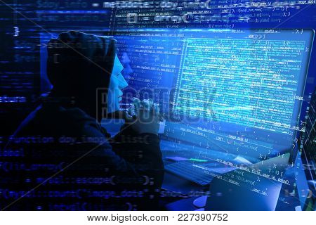 Hacker in mask using computer in darkness. Concept of cyber attack and security