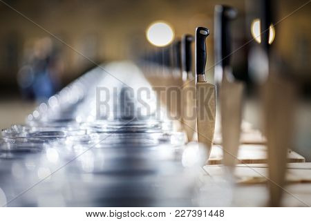 Shiny Metal Knives Stuck In A Table, Perspective With Glassware