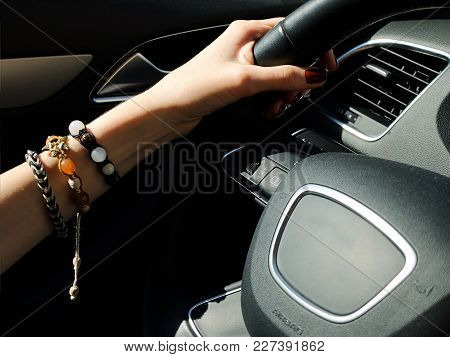 Female Left Hand With The Three Bracelets On The Steering Wheel Of Expensive German Car