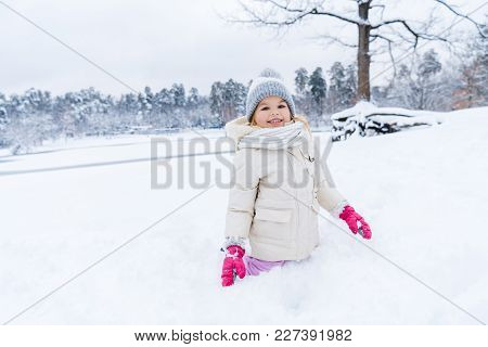 Beautiful Kid Smiling At Camera While Playing And Kneeling In Show