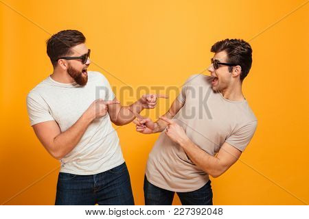 Portrait of a two excited young men in sunglasses pointing fingers at each other isolated over yellow background