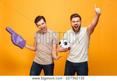Portrait of a two excited young men holding soccer ball and foam glove isolated over yellow background