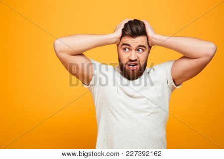 Portrait of a puzzled bearded man holding hands on his head isolated over yellow background