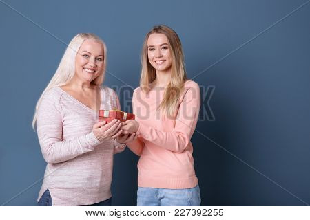 Young daughter and mother with gift box on color background