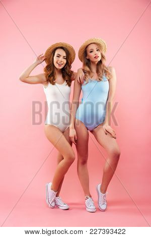 Full-length photo of two fabulous girls 20s in colorful one-piece swimsuits and straw hats posing with lovely look and smile isolated over pink background