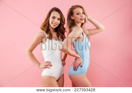 Two brunette and blonde women wearing colorful one-piece swimsuits posing with sexual look while resting on beach isolated over pink background