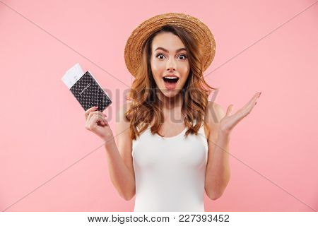 Excited slim woman in white swimsuit and straw hat rejoicing summer holiday with passport and tickets in hand, isolated over pink background