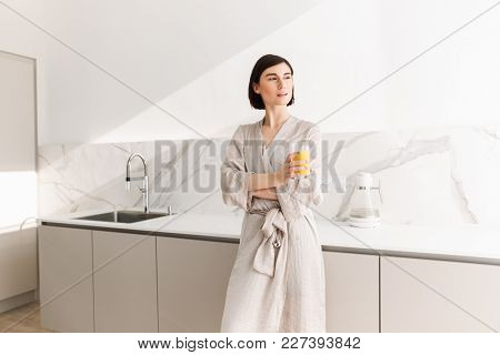 Image of fascinating woman with short dark hair standing in kitchen and drinking orange juice from transparent glass
