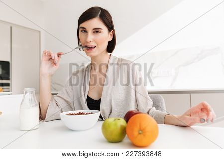 Beautiful caucasian woman having breakfast in kitchen of hotel apartment while eating cocoa balls with milk and fruits
