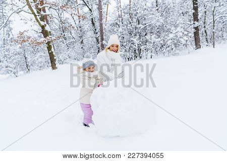 Beautiful Happy Mother And Daughter Making Snowman In Winter Park