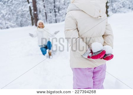 Cropped Shot Of Little Daughter Holding Snowballs And Happy Mother Kneeling Behind In Winter Park