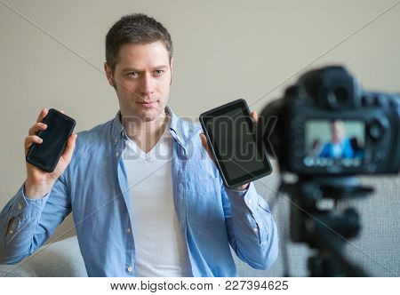 Man Making Video Blog About Difference Between Tablet Pc And Mobile Phone.