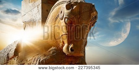 Fragment Of The Statue Of A Horse In Ancient Persepolis Against The Background Of The Sun And The Mo
