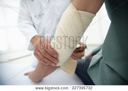 Orthopedist applying bandage onto patient's hand in clinic