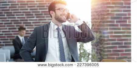 businessman talking on smartphone in his office