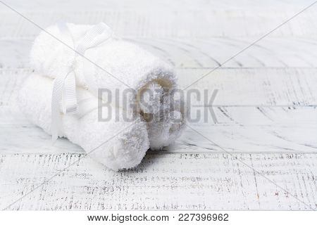 White Cotton Towels And Branch Of Cotton On Wooden Table. Spa Or Body Card Concept. Copy Space