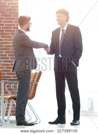 Two business people shake hands in the office