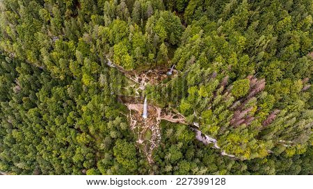Aerial View Of Double Water Fall In A Forest. River Flowing Through Pine Trees.