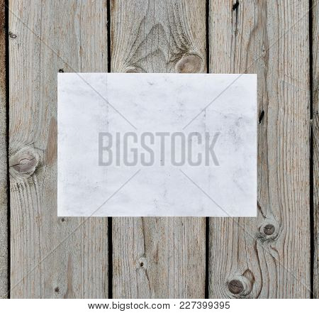 A Sheet Of Pure White Paper Is Horizontally Glued To The Wall Of Old Wooden Boards