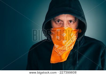 Portrait Of Masked Criminal Male Person Looking At Camera. Adult Man With Hoodie And Scarf Over Face