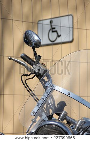 Rear view mirror on motorcycle and badge of disabled person