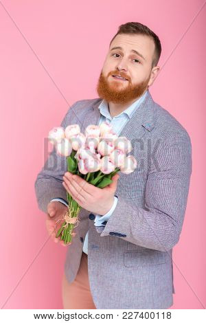 Handsome Bearded Man Holding Bouquet Of Tulips In Hand On Pink Background. Womens Day. 8 March