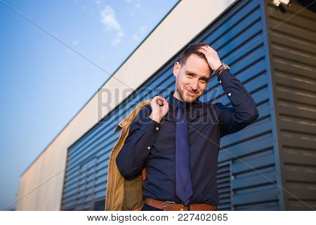 Handsome Elegant Businessman Smiling In Front Of A Building And Wearing Casual Style Outfit