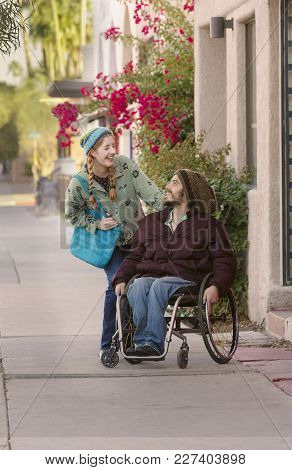 Woman Wearing Hat With Friend In Wheelchair Laughing
