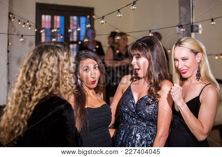 Four Shocked Women Sharing Gossip Or Joke At A Party