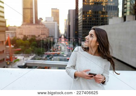 Beautiful young woman sitting on a bridge across the boulevard in urban scenery, downtown, at sunset