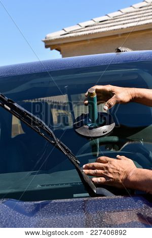 Using Suction Cup In The Process Of Installing A New Windshield On A Pickup