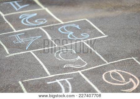 Close-up Photo Of Chalk-painted Hopscotch On Asphalt. School Yard.