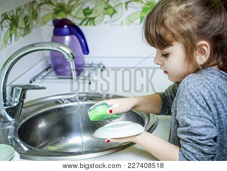 The Little Girl Carefully Washes Dishes In The Kitchen.