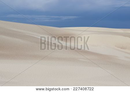 Clean Coast View With Wet Sand And Rainy Sky