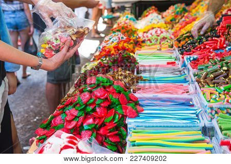 Customers Choose Sweets From Counter With Assorted Colorful Different Shape Jelly Candies On Market