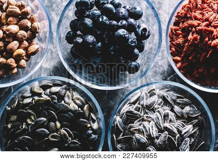 Five glass bowls of different superfoods. Brasilian nuts and almonds, blueberries, goji berries, pumpkin and sunflower seeds.