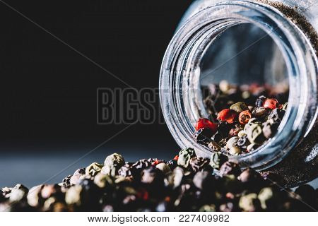 Mixed peppercorns spilling from a glass jar on the kitchen counter. Seasoning.