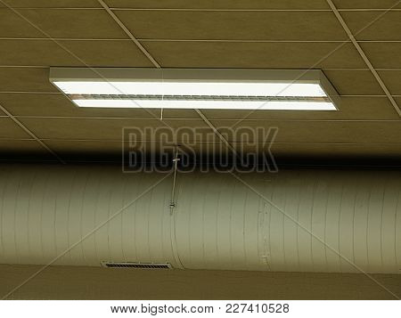 Fluorescent Light Fixture On A White Ceiling. Industrial Lighting In Warehouse