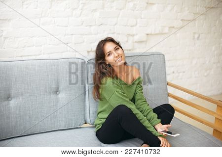 Indoor Shot Of Attractive Carefree Young Mixed Race Lady With Brunette Hair Relaxing On Comfortable