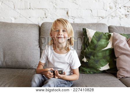 Childhood, Leisure, Music And Modern Technology Concept. Indoor Shot Of Adorable Happy Blonde Male K